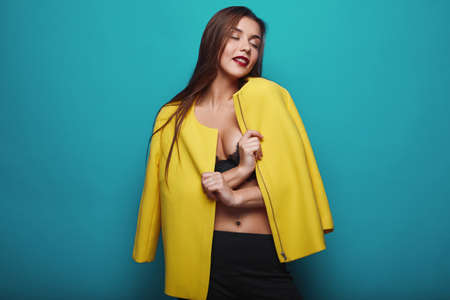 naughty girl: Portrait of fashion glamor stylish swag young woman in yellow coat  on bright background