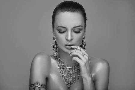 Beauty portrait of young swag woman with jewelry in studio, grayscale color