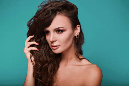 swag: Beauty portrait of young swag woman with curly long hair on bright background in studio. Stock Photo