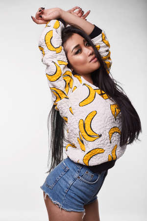 hot asian: Fashion swag portrait of beautiful elegant asian woman in funny banana t-shirt on white background