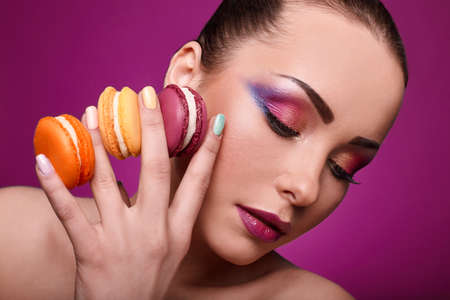 french manicure sexy woman: Beauty glamor fashion model girl with colourful makeup and manicure taking colorful macaroons. Studio shoot.Diet,dieting concept. Sweets.