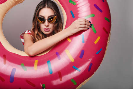 holiday party: Studio bright summer fashion portrait of stylish beautiful woman with make up, colorful sunglasses on bright background