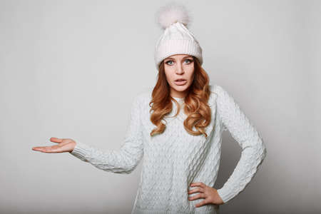 beautiful redhead: Portrait of beautiful redhead woman in white sweater and hat Stock Photo