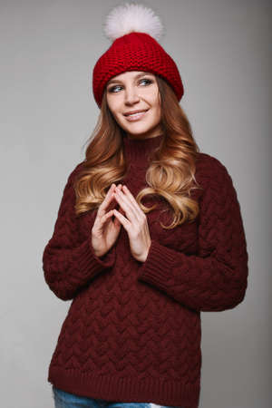 beautiful redhead: Portrait of beautiful redhead woman in red sweater and hat Stock Photo