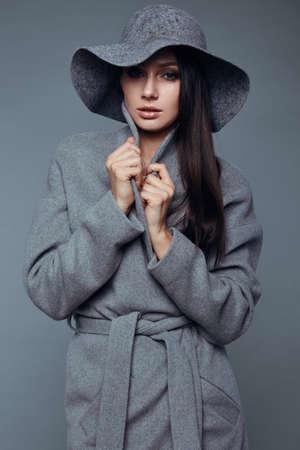 labios sensuales: joven morena de moda mujer de la belleza del retrato en estudio llevar a capa y sombrero gris