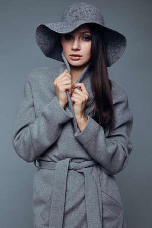 sexy glamour model: young fashion brunette woman beauty portrait posing in studio wearing in gray coat and hat