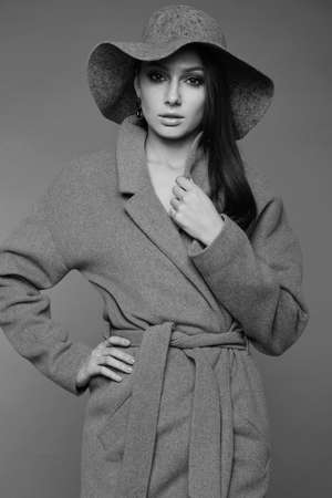 young fashion brunette woman beauty grayscale portrait posing in studio wearing in gray coat and hat
