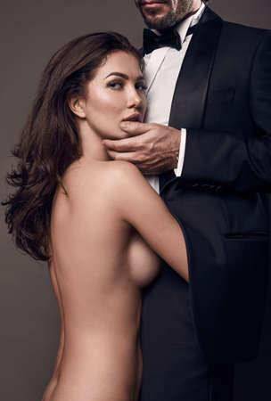 Modernes Portrait elegant sexy Paar im Studio. Blanke schöne Frau, die einen brutalen Mann im Anzug auf einem dunklen Hintergrund umarmt