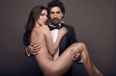 Fashionable portrait of elegant sexy couple in studio. Naked beautiful woman at the hands of a brutal man in suit on dark background Standard-Bild