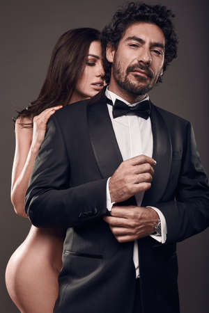 Fashionable portrait of elegant couple in studio. Naked beautiful woman touching a brutal man in suit on dark background