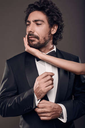 sexual intimacy: Fashionable portrait of elegant sexy couple in studio. Brutal man in suit with womans hand touching his face on dark background