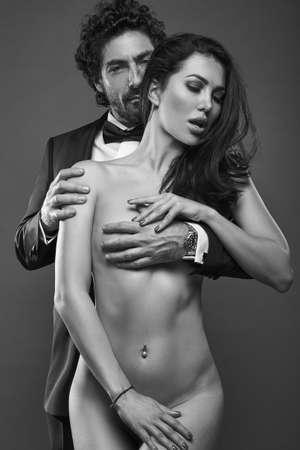 Modische Porträt von eleganten sexy Paar im Studio. Brutaler Mann im Anzug umarmt eine nackte Frau von hinten auf dunklem Hintergrund. Graustufen Lizenzfreie Bilder