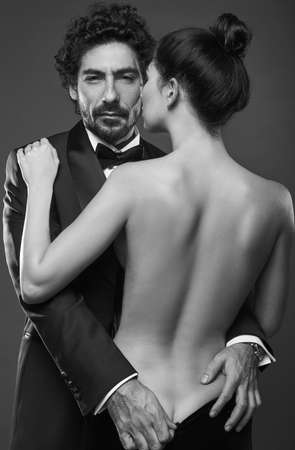Fashionable portrait of elegant sexy couple in studio. Brutal man in suit touching a naked womans back in dress on dark background. Grayscale Standard-Bild