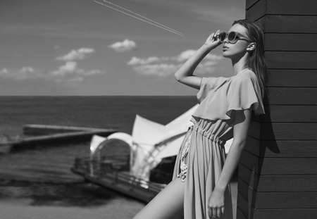 pareo: Fashion, seductive girl in knitted swimsuit and pareo getting a suntan on the beach. grayscale Stock Photo