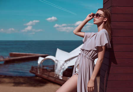 pareo: Fashion, seductive girl in knitted swimsuit and pareo getting a suntan on the beach. Stock Photo