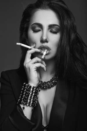 jewerly: Elegant hot brunette woman smoking a cigarette on black background in studio