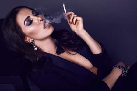 Elegant hot brunette woman smoking a cigarette on black background in studio