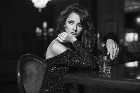 Schoonheid jonge brunette vrouw zitten aan de bar met een glas whisky in luxe interieur