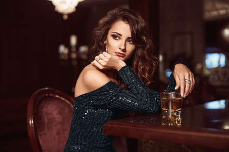 Beauty young brunette woman sitting at the bar with glass of whiskey in luxury interior
