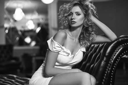 vestido de noche: hermosa mujer joven de moda con el pelo rubio rizado en el sofá de cuero negro Foto de archivo
