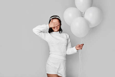 Beautiful fashion model girl with white balloons posing isolated on white background.