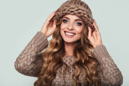 pullover: Portrait of beautiful smiling blond woman with long hair, brown sweater and hat