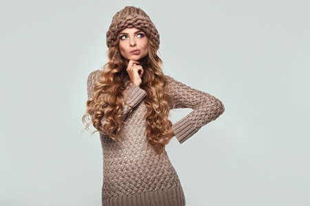 Portrait of beautiful thoughtful blond woman with long hair, brown sweater and hat Stock Photo