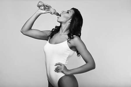 Portrait of young fitness woman wearing sportswear with bottle isolated on white Stock Photo