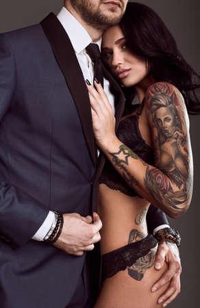 Portrait eines schönen Paares: brutal Mann im eleganten Anzug und sexy Mädchen mit einer Tätowierung in Dessous auf grauem Hintergrund Lizenzfreie Bilder