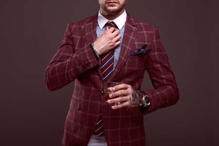 Portrait der eleganten brutalen Mann in einem teuren Anzug aus Wolle mit Glas Whisky auf einem grauen Hintergrund
