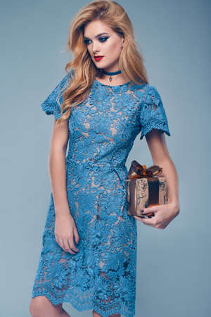 christmas perfume: Portrait of beautiful elegant woman in fashionable blue dress with gift on color background in studio