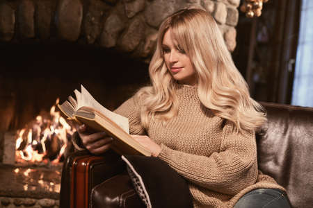 Portrait of georgeous elegant blonde reading book near the cozy fireplace. Interior shoot Stock Photo