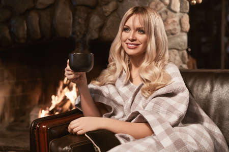Portrait of georgeous elegant blonde under bright plaid with cup of tea near the cozy fireplace. Interior shoot