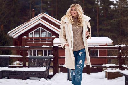 Portrait of georgeous elegant blonde in bright dress on winter ski resort house background
