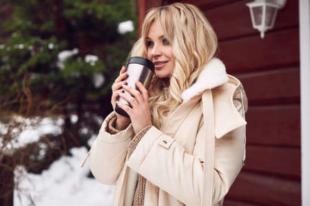 Portrait of georgeous elegant blonde in bright dress with cup of tea on ski resort house background