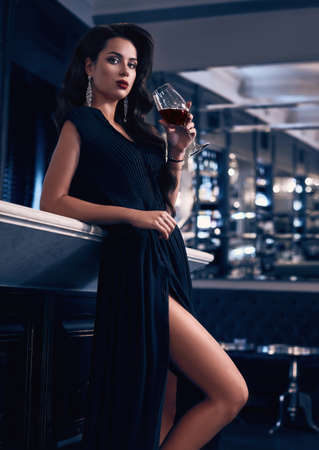 Gorgeous beauty young brunette woman in dark dress with glass of wine standing at the bar in luxury interior