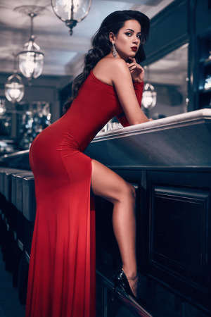 Gorgeous beauty young brunette woman in red dress standing at the bar in luxury interior