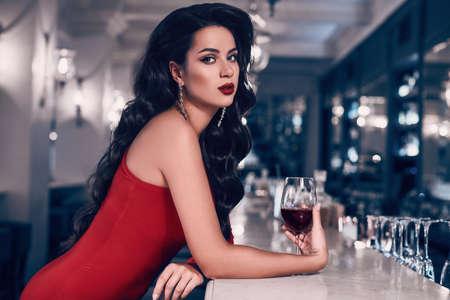 Schitterende schoonheids jonge donkerbruine vrouw in rode kleding met glas wijn die zich bij de bar in luxebinnenland bevinden