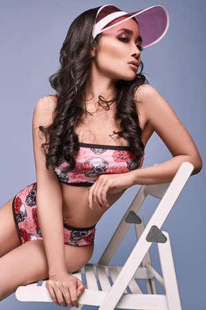 Glamorous fashion portrait of beautiful charming asian girl in colorful swimsuit with chair on a bright background in the studio Lizenzfreie Bilder
