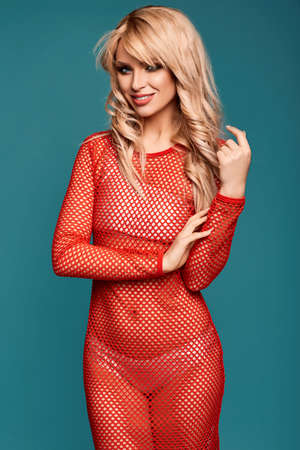 Glamorous fashion portrait of beautiful charming blonde girl in colorful beach dress on a bright background in the studio