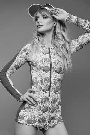 Glamouröse Mode Porträt der schönen charmante blonde Mädchen in bunten Badeanzug auf einem hellen Hintergrund im Studio