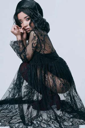 retrato de moda atractiva de hermosa chica asiática hermosa en vestido largo negro y sombrero de cuero aislado en el fondo blanco Foto de archivo