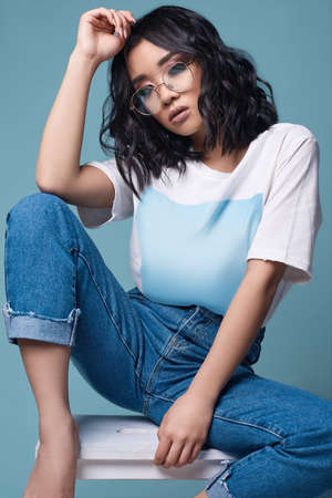 Fashionable portrait of elegant sexy asian girl in jeans and white t-shirt isolated on bright mint background Stockfoto