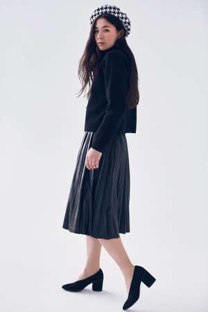ファッショナブルな黒いスカートと白い背景に分離ベレートでエレガントなアジアの女性のゴージャスな肖像画