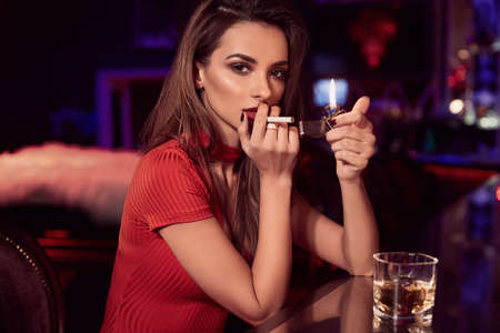 Portrait of gorgeous beauty young brunette woman in red dress sitting at the bar with cigarette and glass of whiskey in luxury interior