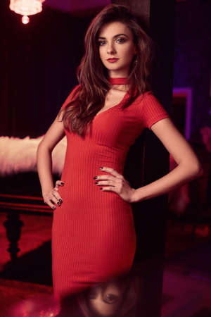 Portrait of gorgeous beauty young brunette woman wearing red dress in luxury interior Standard-Bild