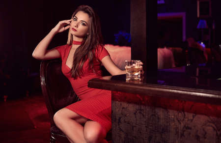 Portrait of gorgeous beauty young brunette woman in red dress sitting at the bar with glass of whiskey in luxury interior