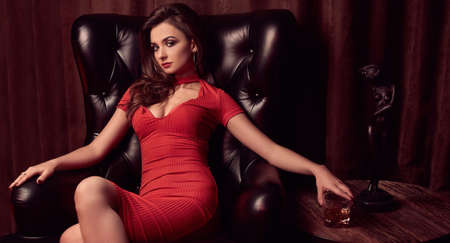 Portrait of gorgeous beauty young brunette woman in red dress sitting in a leather chair with glass of whiskey in luxury interior