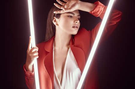 Porträt der eleganten schönen Frau in einem roten modischen Anzug, der um leuchtende Neonlichter aufwirft