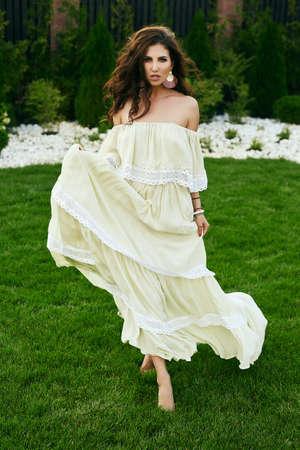 Portrait of gorgeous sensual brunette model in fashion dress posing in garden